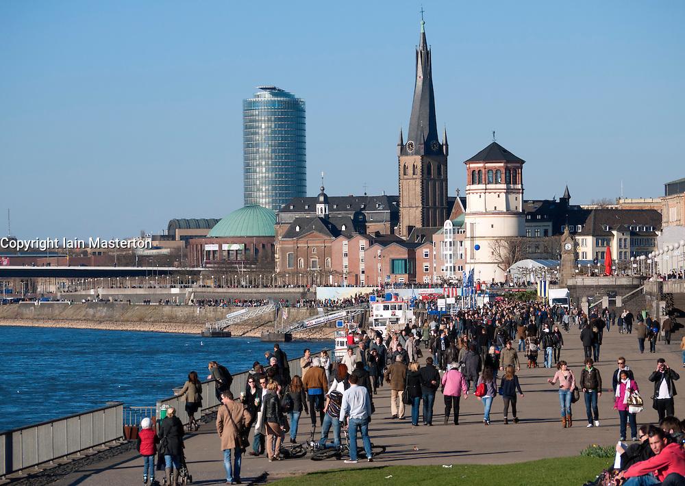 People walking and relaxing beside the River Rhine in Dusseldorf Germany