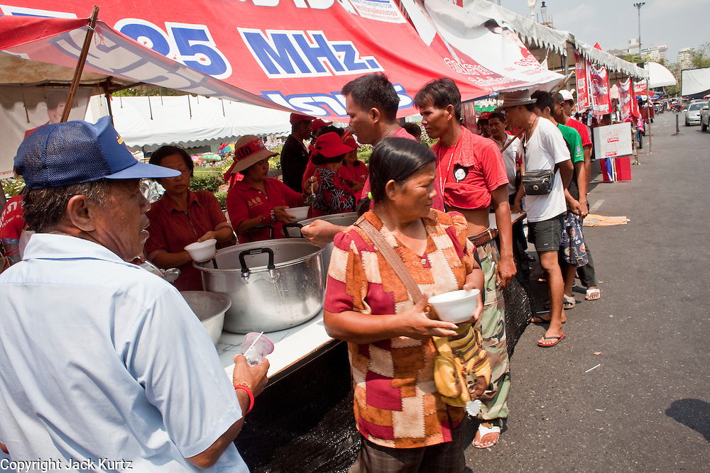 """Apr. 1, 2010 - BANGKOK, THAILAND: Red Shirts line up for lunch at one of the several canteens that are feeding the Red Shirt protestors in Bangkok. Fewer than 5,000 """"Red Shirts,"""" members of the UDD (National United Front of Democracy Against Dictatorship) continue to protest at Phan Fa Bridge in central Bangkok to demand the resignation of current Thai Prime Minister Abhisit Vejjajiva and his government. The protest is a continuation of protests the Red Shirts have been holding across Thailand. They support former Prime Minister Thaksin Shinawatra, who was deposed in a coup in 2006 and went into exile rather than go to prison after being convicted on corruption charges. Thaksin is still enormously popular in rural Thailand.  The leaders of the Red Shirts have promised to gridlock Bangkok with another massive rally this weekend.     PHOTO BY JACK KURTZ"""