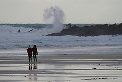 © Licensed to London News Pictures. 17/12/2011. St Ives, UK. Two people walk on Porthmeor Beach as wave crashes against 'The Island', St Ives where winds are forecast to reach up to 40 mph. Photo credit : Ashley Hugo/LNP