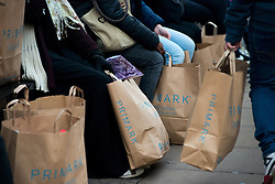 © Licensed to London News Pictures.17/12/2013. London, UK. Shoppers rest with shopping bags on Oxford Street only a week before Christmas.Photo credit : Peter Kollanyi/LNP