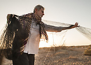 The Ornithologist sets up nets to catch birds in the early morning.