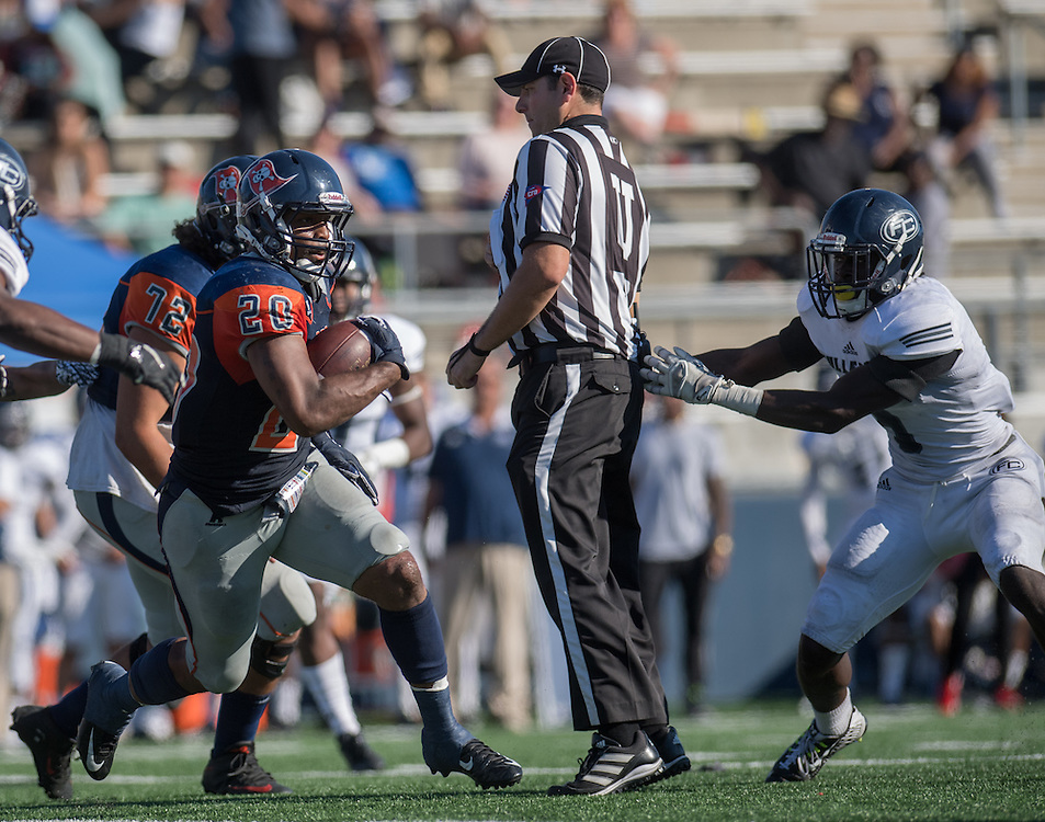 Costa Mesa, CA - Orange Coast College running back Derrick Hunt (20) runs during OCC's November 5th game against Orange Empire Conference rival Fullerton College while Fullerton defensive back Javon Burriss (right) pushes the field umpire aside. Fullerton won the game, 35-14.