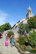 Mature woman and two children walking towards Church of Saint Martin (Sveti Martin), Zrnovo, island of Korcula, Croatia