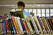 An inmate chooses a book from the prison library. HMP Wandsworth, London, United Kingdom.