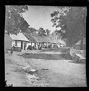 Prosperous looking people sitting outside thatched workers' one storey whitewashed cottages, possibly tourists to the Lake District, England, UK late 1800s c 1900