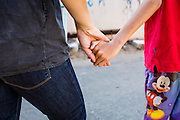 28 MARCH 2013 - BANGKOK, THAILAND: Michelle Kao holds hands with a child who lives in her neighborhood.      PHOTO BY JACK KURTZ