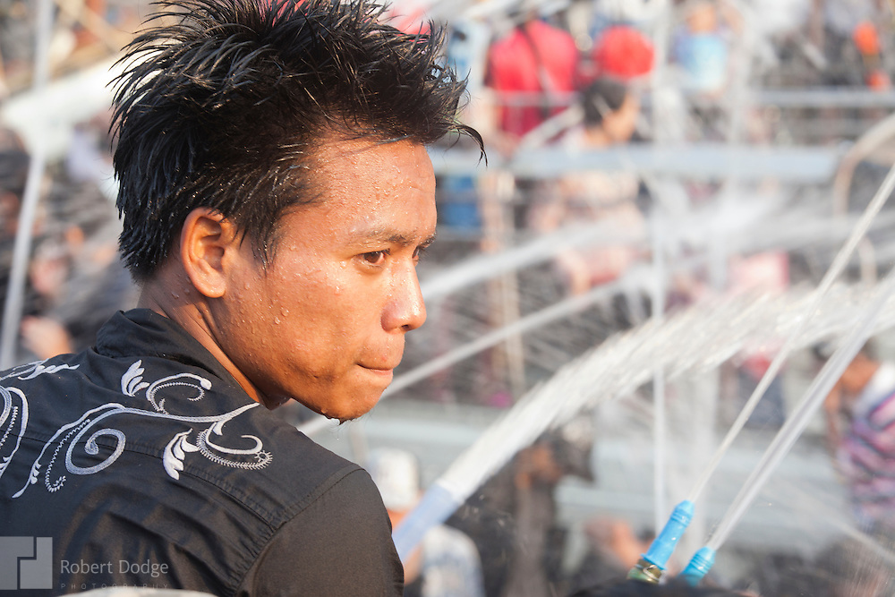 Mandalay, Myanmar- April 14, 2013: A young man watches the flow of water from high-powered hoses showering celebrants during Myanmar's Thingyan Water Festival. Thingyan is held in April, one of the hottest months of the year in Myanmar. The water festival marks the country's New Year celebration and the festival includes lots of drinking, singing, dancing and theater. Wherever you are you are likely to get doused with water as the Burmese see this as a cleansing of the previous year's sins and bad luck and a blessing for good luck and prosperity in the year ahead. In the major cities of Mandalay and Yangon, large platforms are erected along major roadways and are equipped with high powered water hoses. The platforms, sponsored by large corporate donors, also have dance stages and play the latest pop and hip hop music. Thousands of residents pour into the streets by foot, motorbike and flatbed truck to get hosed under the platforms while they drink and dance. Many of the young celebrants wear their best clubbing clothes. And many of the party goers are men, having left their wives and girlfriends at home.