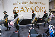 """01 JUNE 2014 - BANGKOK, THAILAND: Thai troops move into position at Gaysorn, a high end shopping mall in Bangkok. The Thai army seized power in a coup that unseated a democratically elected government on May 22. Since then there have been sporadic protests against the coup. The protests Sunday were the largest in several days and seemed to be spontaneous """"flash mobs"""" that appeared at shopping centers in Bangkok and then broke up when soldiers arrived. Protest against the coup is illegal and the junta has threatened to arrest anyone who protests the coup. There was a massive security operation in Bangkok Sunday that shut down several shopping areas to prevent the protests but protestors went to malls that had no military presence.    PHOTO BY JACK KURTZ"""