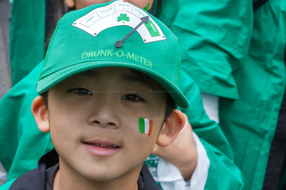 """A little boy in a """"drunk-o-meter"""" hat enjoys the 27th Saint .Patrick's Day Parade in Omotesando, Tokyo, Japan. Sunday March 17th 2019. Started in 1992 by the Irish Network, Japan, and supported by the Embassy of Ireland,; the parade, along with the """"I Love Ireland Festival"""" held nearby is Asia's  largest Irish event."""