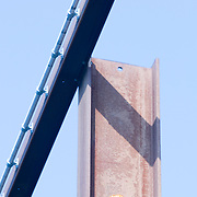view from below of steel girder and crane with blue sky background