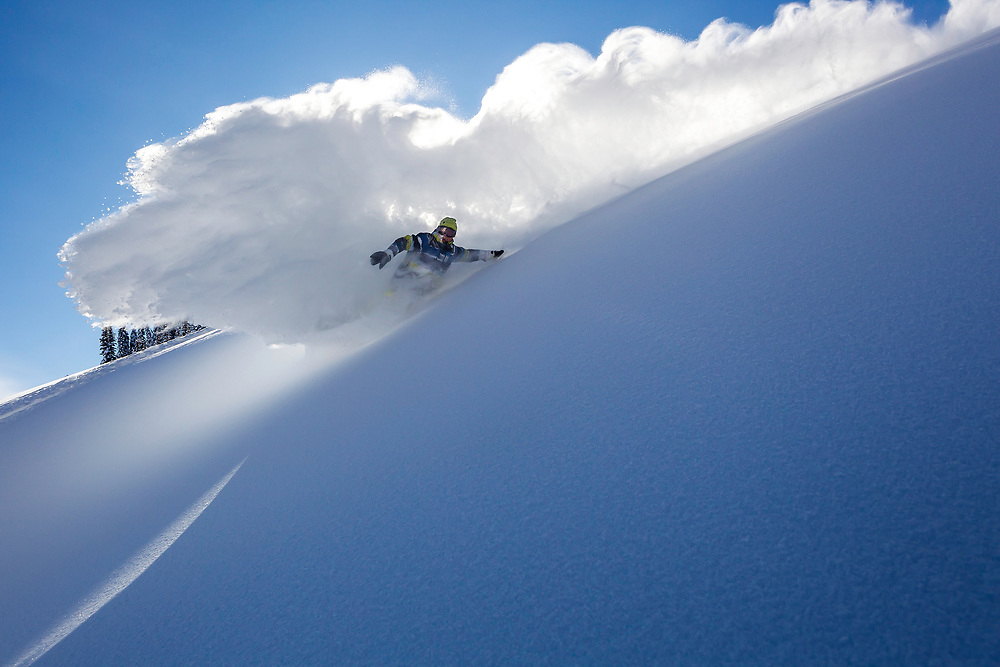 Professional snowboarder Travis Rice slashes a ridge on his snowboard while filming in his home town of Jackson Hole, Wyoming.
