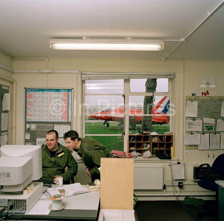 Engineering ground staff of the Red Arrows, Britain's RAF aerobatic team, consult technical information on Ministry of Defence (MoD) computers. Outside the old building's windows (once the hangars of the famous Dambusters 617 Squadron) is an old Gnat once used by the team. They are members of the team's support ground crew who outnumber the pilots 8:1 and without them, the Red Arrows couldn't fly.  Eleven trades are imported from some sixty that the RAF employs and teaches. Eleven trades are imported from some sixty that the RAF employs and teaches.