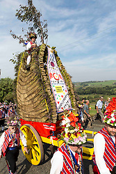 © Licensed to London News Pictures. 23/08/2015 . Uppermill , Saddleworth , Greater Manchester , UK. <br /> The Saddleworth Ruschart Festival in Uppermill today (Sunday 23rd Aug 2015).<br /> A rushcart built of moorland rushes is pulled by Morris Dancers from Uppermill village square to St Chad's Church.  The tradition arises from the laying of rushes on the church floor to keep it warm in winter.<br /> <br /> Photo credit : Photographers Chris Bull / LNP