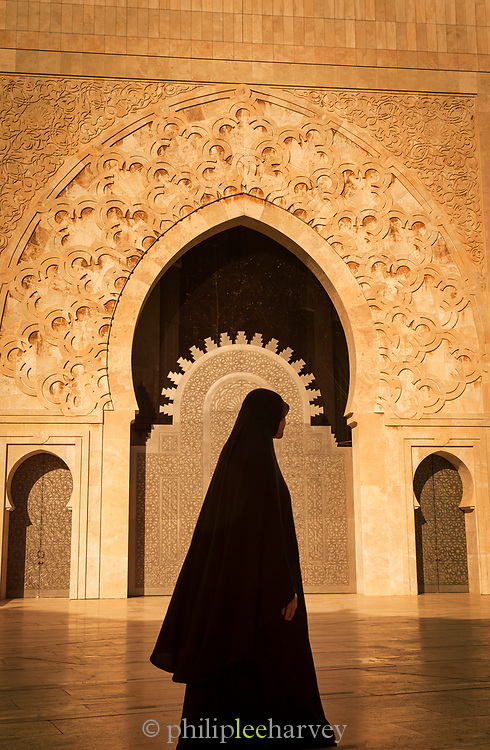 Side view of woman wearing traditional clothes in front of Hassan II Mosque in Casablanca, Morocco
