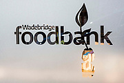 Wadebridge foodbank sign in the window of the Trussell Trust foodbank and storehouse in Bridgend, Cornwall, United Kingdom.  This foodbank provides emergency food parcels for individuals and families in crisis in Bodmin, Camelford, Padstow and Wadebridge.