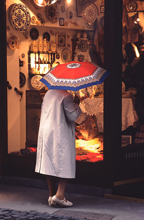 Older woman window shops in Mainz, Germany protected by a raincoat and red, blue, white and yellow umbrella. The store is filled with decorations, artisan pieces, plates, framed artwork, vases, and a table with a lace tablecloth.