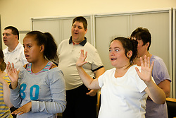 Group of Day Service users with learning disabilities using makaton a way of communicating with signs and symbols specially for people with learning difficulties,