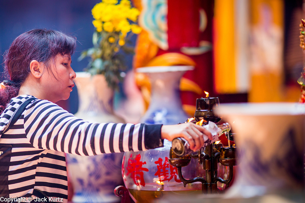 """12 APRIL 2012 - HO CHI MINH CITY, VIETNAM: A woman pours holy oil over a lamp in Quan Am Pagoda. Chùa Quan Âm (Avalokiteshvara Pagoda), a Chinese style Buddhist pagoda in Cho Lon. Founded in the 19th century, it is dedicated to the bodhisattva Quan Âm. The pagoda is very popular among both Vietnamese and Chinese Buddhists. Cholon is the Chinese-influenced section of Ho Chi Minh City (former Saigon). It is the largest """"Chinatown"""" in Vietnam. Cholon consists of the western half of District 5 as well as several adjoining neighborhoods in District 6. The Vietnamese name Cholon literally means """"big"""" (lon) """"market"""" (cho). Incorporated in 1879 as a city 11km from central Saigon. By the 1930s, it had expanded to the city limit of Saigon. On April 27, 1931, French colonial authorities merged the two cities to form Saigon-Cholon. In 1956, """"Cholon"""" was dropped from the name and the city became known as Saigon. During the Vietnam War (called the American War by the Vietnamese), soldiers and deserters from the United States Army maintained a thriving black market in Cholon, trading in various American and especially U.S Army-issue items.          PHOTO BY JACK KURTZ"""