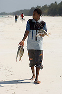 A man walking along the beach with his catch of the day.  Jambiani, Zanzibar, Tanzania