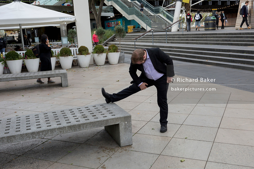 A man wearing a suit makes a hamstring stretch on the Southbank, on 21st September 2018, in London England