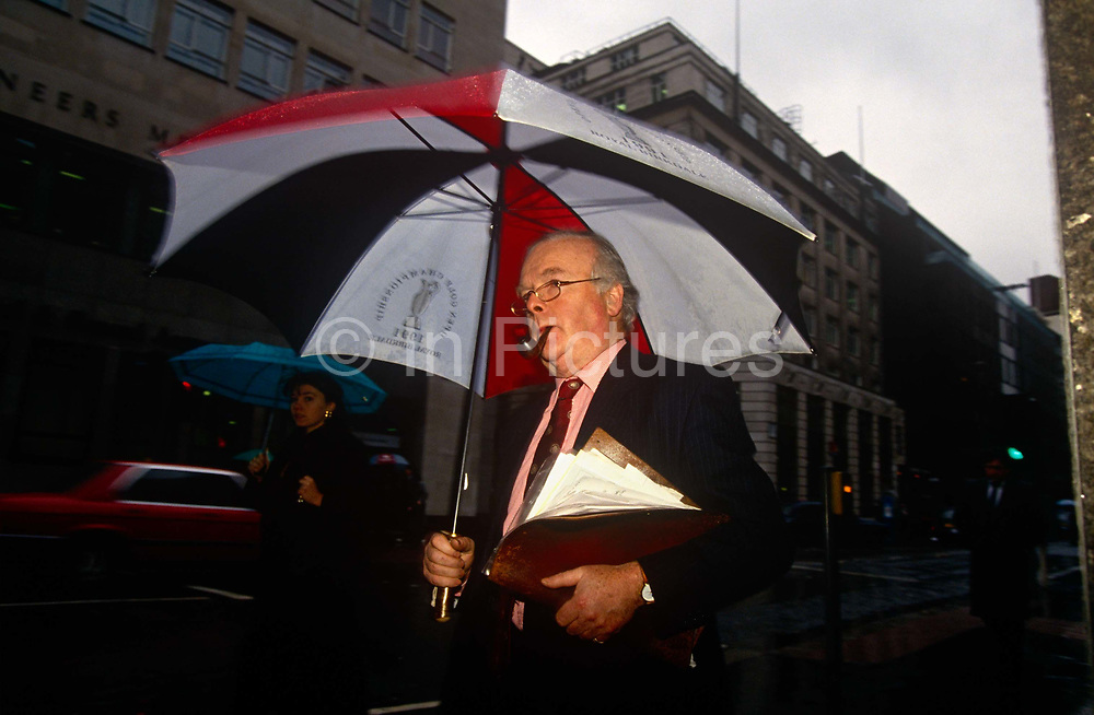 A male office worker walks through a darkening winter afternoon in the rain in the City of London. Holding a large corporate brolley and sucking on a pipe in his mouth, the middle-aged gent walks briskly along en route to a meeting with associates elsewhere.