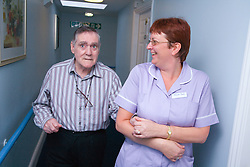 Care Assistant leading a man with Alzheimer's Disease down the corridor of a nursing home,