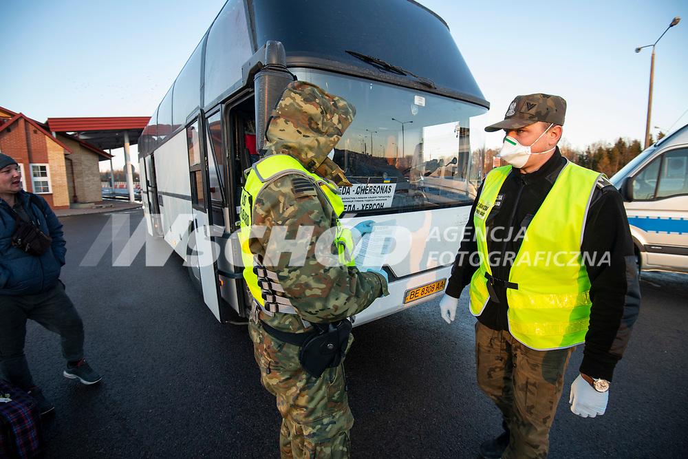 Budzisko, woj podlaskie, 14.03.2020. Od polnocy zostanie przywrocona kontrola graniczna na wewnetrznej granicy UE na dawnym przejsciu granicznym z Litwa N/z grupa ukrainskich kierwocow wracajacych ze szkolenia na Litwie przekorczyla grance pieszo ( kierowca busa ktory ich wiozl do Suwalk myslal,ze granica jest juz zamknieta i wysadzil ich wczesniej ), potem wsiedli do rejsowego autobusu z Klajpedy; polska Straza Graniczna sprawdza ich dokumenty fot Michal Kosc / AGENCJA WSCHOD