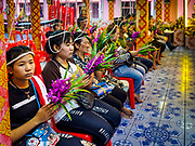 """29 MARCH 2017 - BANG KRUAI, NONTHABURI, THAILAND:  People pray during a """"Resurrection Ceremony"""" at Wat Ta Kien (also spelled Wat Tahkian), a Buddhist temple in the suburbs of Bangkok. People go to the temple to participate in a """"Resurrection Ceremony."""" Thai Buddhists believe that connecting people by strings around their heads, which are connected to a web of strings suspended from the ceiling, amplifies the power of the prayer. Groups of people meet and pray with the temple's Buddhist monks. Then they lie in coffins, the monks pull a pink sheet over them, symbolizing their ritualistic death. The sheet is then pulled back, and people sit up in the coffin, symbolizing their ritualist rebirth. The ceremony is supposed to expunge bad karma and bad luck from a person's life and also get people used to the idea of the inevitability of death. Most times, one person lays in one coffin, but there is family sized coffin that can accommodate up to six people. The temple has been doing the resurrection ceremonies for about nine years.         PHOTO BY JACK KURTZ"""