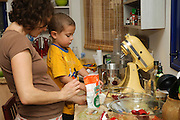 Mother and son work together in the kitchen backing a cake - Model release available