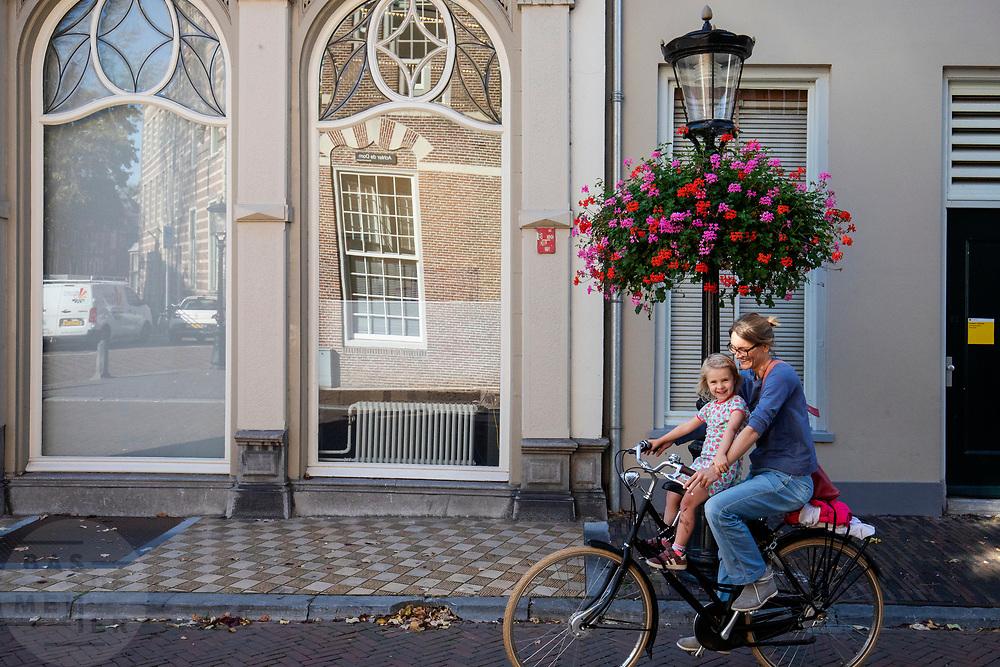 Een vrouw fietst met een meisje voorop door Utrecht.<br /> <br /> A woman cycles with a girl on the front seat of the bike in Utrecht.
