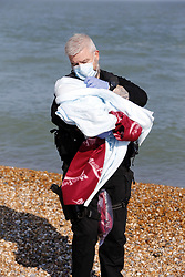 © Licensed to London News Pictures. 09/10/2021. Dungeness, UK. A 14 day old migrant baby girl named Alana is carried ashore by a Border Force officer at Dungeness in Kent after crossing the English Channel. Alana travelled with her parents from Iraq and spent 9 hours on the water before rescue by the RNLI. Hundreds of migrants have made the crossing in the calm weather this week. Photo credit: Sean Aidan/LNP