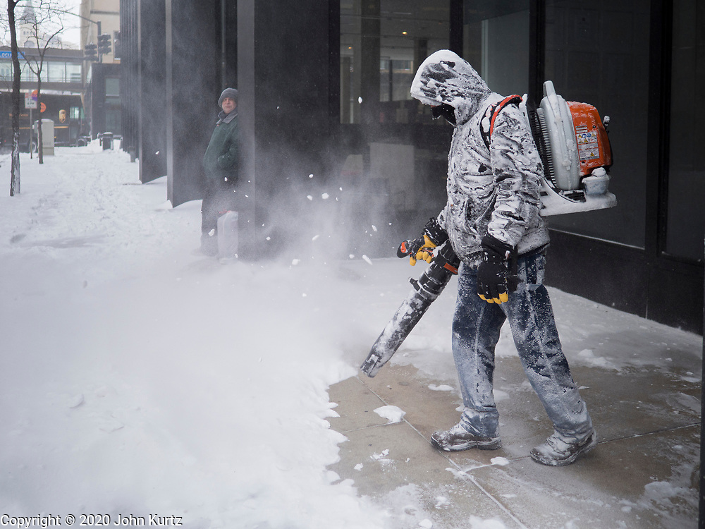 17 JANUARY 2020 - DES MOINES, IOWA: A worker uses a blower to clear the sidewalk in front of an office building in downtown Des Moines. The second significant snow fall in a week hit central Iowa Friday. The snow started falling during the morning rush hour and by early afternoon about five inches had fallen in Des Moines. Meteorologists said up to 1/10 of an inch of ice could cover the snow by the end of the day. The snowstorm was expected to turn into a blizzard in northern Iowa on Saturday with wind speeds above 30MPH. Many businesses in the Des Moines area closed early Friday and several of the Democratic presidential candidates cancelled their campaign events because of the snow.      PHOTO BY JACK KURTZ