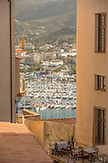Harbor and tables with chairs on street from citadel, Calvi, Corsica, France