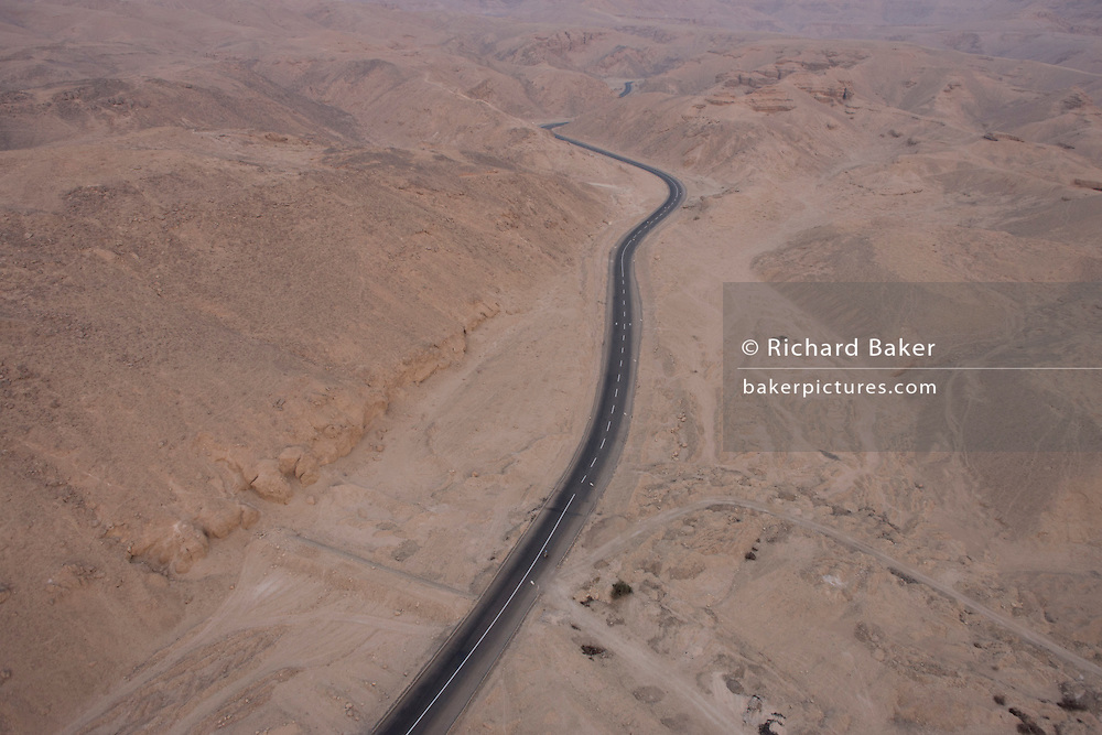 An aerial dawn landscape, looking down from a hot air balloon on to the road to the Valley of the Kings o the West Bank of the modern city of Luxor, Nile Valley, Egypt. n