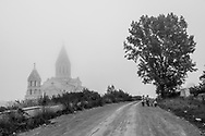 On a misty afternoon, women and children walk past the Holy Savior Cathedral, or Ghazanchetsots Cathedral, in Shushi (Shusha), in the disputed region of Nagorno-Karabakh. Built in the 1880s, it is the seat of the Diocese of Artsakh of the Armenian Apostolic Church.<br /> <br /> (September 23, 2016)