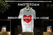 Nederland, Amsterdam, 7-5-2020 In een etalage van een ticketbureau wat ook bezoeken aan het gesloten Anne Frank huis verkoopt in de oude binnenstad is een tshirt met een rood hart opgehangen als dank en respectbetuiging aan het personeel in de zorg en op de ic die met het coronavirus te maken hebben . Foto: Flip Franssen
