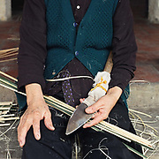 A woman preparing bamboo for weaving into baskets in Tang Tien village, Bac Giang province, Vietnam. With Vietnam's growing population making less land available for farmers to work, families unable to sustain themselves are turning to the creation of various products in rural areas.  These 'craft' villages specialise in a single product or activity, anything from palm leaf hats to incense sticks, or from noodle making to snake-catching. Some of these 'craft' villages date back hundreds of years, whilst others are a more recent response to enable rural farmers to earn much needed extra income.