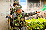 May 19 - BANGKOK, THAILAND: A Thai army officer directs his soldiers into position in Lumpini Park during the Thai government crack down against Red Shirt and anti government protesters. The Royal Thai Army attacked anti-government protesters May 19 with troops and armored personnel carriers. PHOTO BY JACK KURTZ