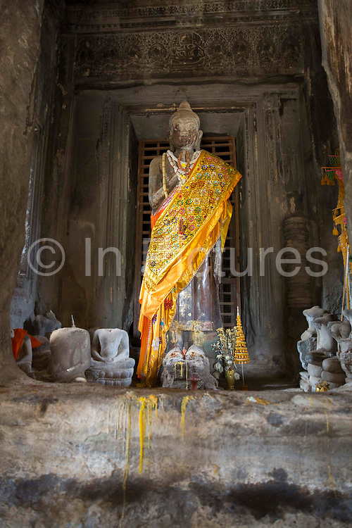 An ancient Buddha statue decorated with yellow cloth within the Angkor Wat temple Siem Reap, Cambodia.  Angkor Wat is one of UNESCO's world heritage sites. It was built in the 12th century initially as a Hindu temple which then transformed into a Buddhist temple by the end of the 12th century. Theravada Buddhism has been the state religion in Cambodia since the 13th century.