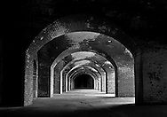 Black and white architectural study of Fort Point, San Francisco; arches, windows and textural brick elements seen in varying degrees of light and shadow
