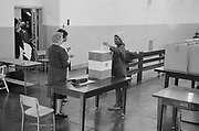 Young African American woman casting her vote in a ballot box at voting station in the Cardoza High School building, Washington. DC, 3 May 1964. Photographer:  Marion S Trikosko.