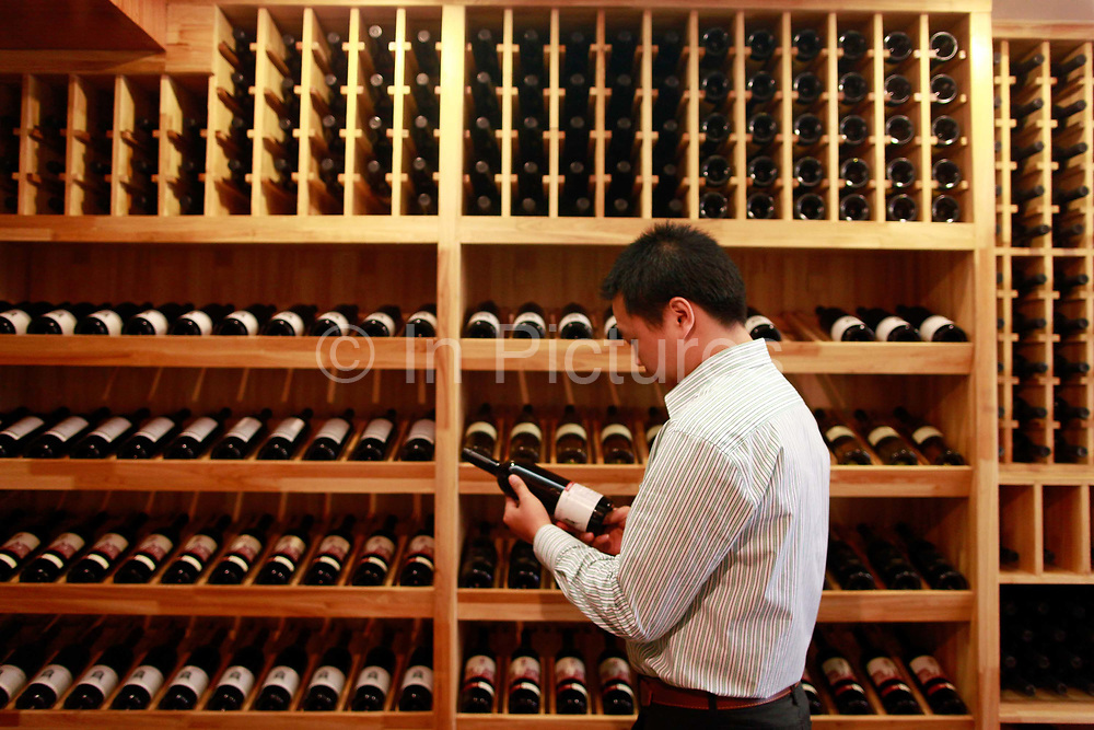 Lin Tiangui, a representative of Winston Wine, looks ar a bottles of wine produced from Winston Wine's own Australian winery at one of its stores in Shanghai, China on 18 October, 2011. Photographer: Qilai Shen/BloombergLin Tiangui, a representative for Australia's Winston Wines Pty, examines a bottle of wine at the company's store in Shanghai, China, on Tuesday, Oct. 18, 2011. Australian vineyards, facing slumping exports and rising competition, are turning to China as Chinese buyers creating surging demand among the nation's rich, who are developing a taste for wine and the expression of wealth and class it conveys.