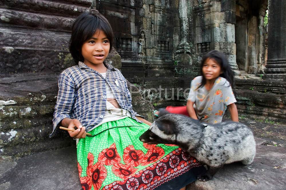 Two girls play with their pet whilst singing songs at the entrance to Preah Khan, a temple built and used by Jayavarman VII. Living there while Angkor Thom was being reconstructed. Once having the role of monastery and university to many thousands, it then became an inter-denominational temple for Buddha, Shiva and Vishnu and the main deity Lokesvara (plus another 282 gods). Today it is in a state of semi-collapse, lichen and moss covered, and with the jungle trees encroaching it's walls.