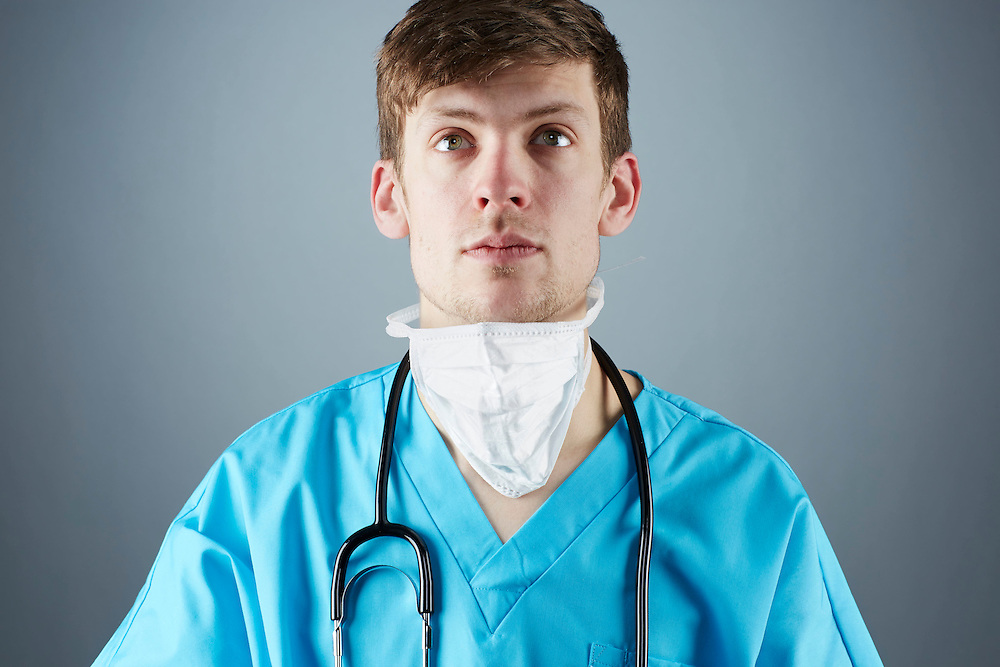 A portrait series representing the intense emotions that Doctors face.  A white male Doctor wearing a white surgical mask, stethoscope, and blue medical scrub suit shown.