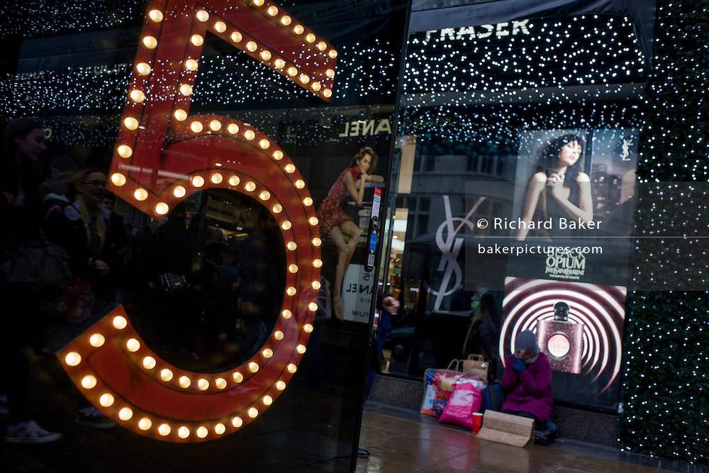 Shoppers with a number Five in the foreground on a bus stop with ads for Yves Saint Laurent in the window of Debenhams in Oxford Street, central London.