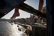 The legs of a local youth before he dives off the Ponte de Dom Luis I bridge and into the cold waters of the River Douro with the city of Porto behind on , on 20th July, in Porto, Portugal. For the price of a Euro, will the boys leap off the girders, into the water - known as tombstoning, due to its obvious dangers. The Dom Luís I or Luiz I Bridge is a double-decked metal arch bridge that spans the Douro River between the cities of Porto and Vila Nova de Gaia in Portugal. At the time of construction its span of 172 m was the longest of its type in the world.