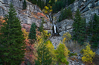A waterfall cascades down through the rocky mountainside surrounded by the beauty of Fall colors in Provo Canyon.