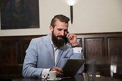 Young man talking on phone while using digital tablet at restaurant
