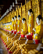 Row of Buddhas along the reverse of the great reclining figure at Chaukhtatgyi Paya. Chaukhtatgyi Buddha Temple is the most well-known Buddhist temple in Bahan Township, Yangon, Yangon Region, Myanmar. It houses one of the most revered reclining Buddha images in the country