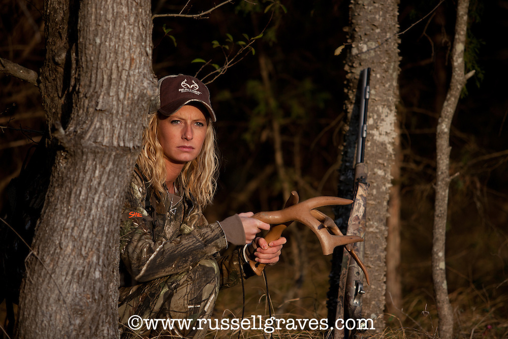 female deer hunter using synthetic rattling antlers